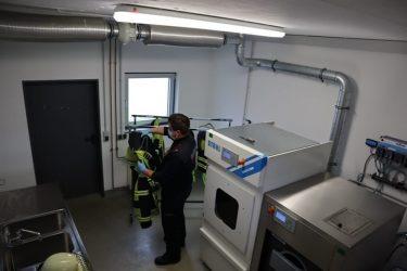 Feuerwehrmann hängt die Jacke auf - Stahl Waeschereimaschinen