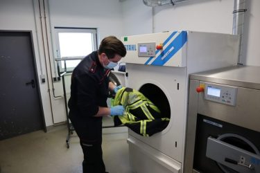 Feuerwehrmann holt eine Jacke aus der Waschmaschine raus